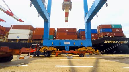 truck crane : International Container ship unloading containers on service trucks at Haifas international port. Stock Footage