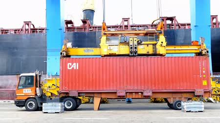truck crane : International Container ship unloading containers on service trucks Stock Footage