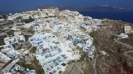 УВР : Aerial footage of Oia, Santorini - Famous white houses and blue domes on the edge of the cliff and blue lagoon.
