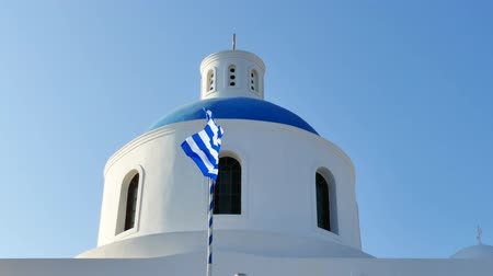 УВР : Greek national flag wavin, with a blue church dome in the background Стоковые видеозаписи