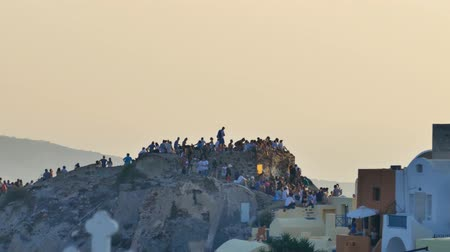 УВР : Smooth Zoom out - Tourists watching the sunset at Oia, Santorini zoomed out to white houses and blue domes of Oia. Стоковые видеозаписи