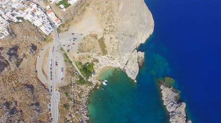 grego : Lindos Acropolis - Aerial footage of the Acropolis, white houses and blue bay of Lindos, Rodos (Greece).