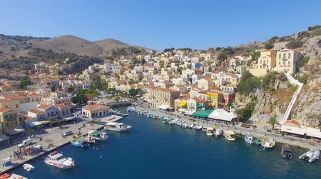 rhodes : Symi island - Aerial footage of Colorful houses and small boats at the heart of the village Stock Footage