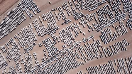 zaparkoval : New cars covered in protective white sheets parked in a holding platform - Aerial footage