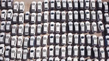 magazyn : New cars covered in protective white sheets parked in a holding platform - Aerial footage