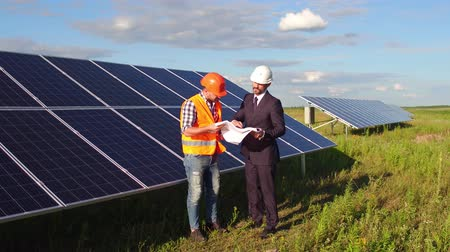 coletor : On footage foreman and business client meeting in the field at solar energy station.