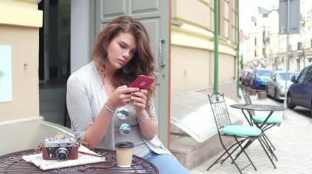 sturen : Pretty young woman sitting at the street cafe in european city.