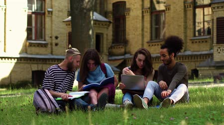 latino americana : Student firends doing homework sitting on grass.