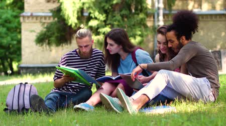 latinamerican : Students reading textbooks while sitting on grass.