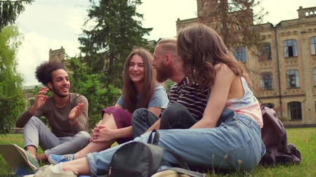latino americana : Students in campus sitting on grass, talking and laughing.