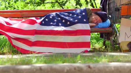 bağımlı : View of a homeless man lying on bench covered with USA flag. Stok Video