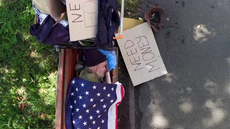 belongings : Top view of a beggar lying on bench, covered with flaf of USA.