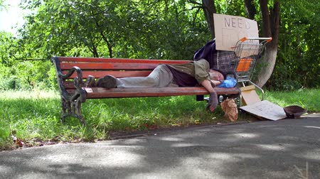 belongings : Footage with old drunk tramp, sleeping on bench in the street. Stock Footage