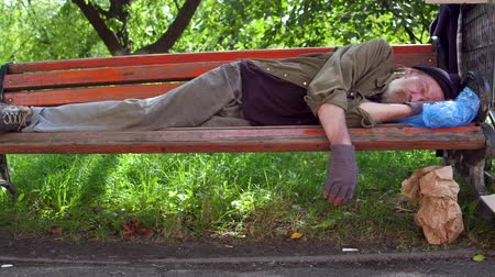 preciso : Beggar on lying on bench, hat with coins and board with sign need money on ground.