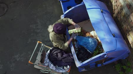 酔った : Top view of homeless man approaching trash can with shopping cart.