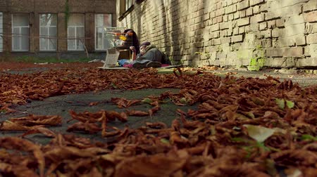 coisas : Fooage of fallen leaves on ground and homeless man sleeping on ground on backdrop. Vídeos