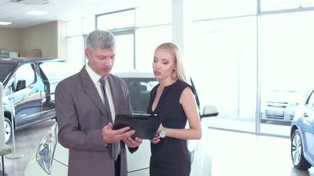 foglalat : Young woman in auto showroom talking with vehicle dealer. Stock mozgókép