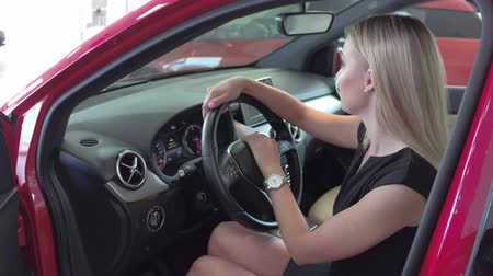 car rental : Attractive woman in auto showroom sitting in the car. Stock Footage