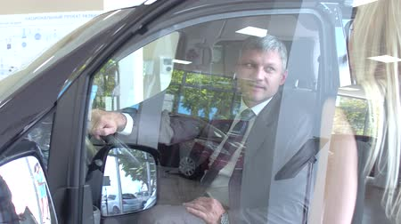 тестирование : View of a dealer showing new car to customer, Стоковые видеозаписи