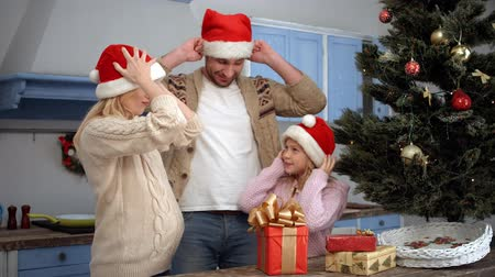 záradék : Happy father giving Santa Clause hats to his wife and daughter while celebrating New Year or Christmas at home all together.