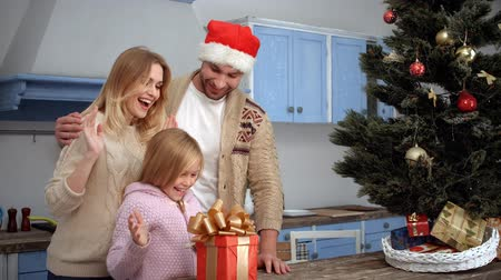 záradék : Family celebrating Christmas and New Year at home. Father with Santa Clause hat on giving New Year or Christmas gift or present to his daughter.