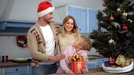 záradék : Mother closing eyes of daughter and father giving New Year or Christmas present to her. New Year or Christmas concept. Santa Clause concept. Stock mozgókép