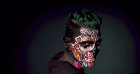 cortiça : Man with bright skull make up and stylish haircut touching head. Concept of face art for Halloween celebration.