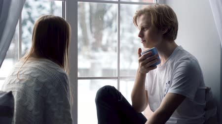 heterosexuální : A cold winter day. Two young belovers sitting on the window sill and looking at each other with deep passion.