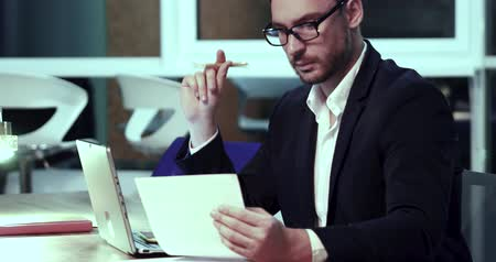 késő : Sales manager in black suit and wearing glasses sits at the office table. Working with pie charts on laptop. Late work overtime concept.