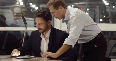 executivo : Two handsome partners are discussing results of the project in late office. Late work overtime concept.