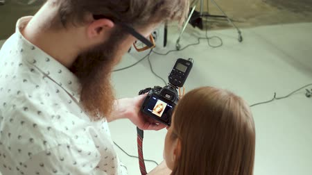 fotoshoot : Photographer in a studio demonstrating photos to a model. Choosing proper photos.