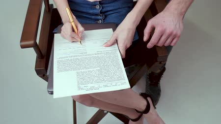 fotoshoot : A beautiful model sitting on a chair and signing agreement. A photographer is next to her.