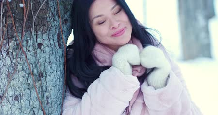 пальто : Portrait of a beautiful Asian woman against the background of the snow park. Snowflakes lie on her hair. She is dressed in a pink coat and white gloves. She holds hair and smile to the camera.