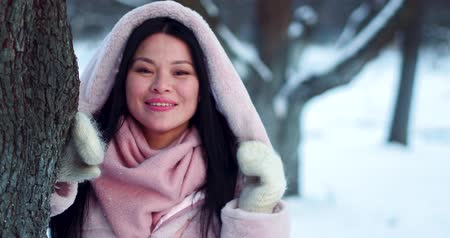 mittens : Beautiful smiling Asian woman enjoys winter and snow in snowy park between trees.