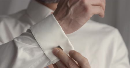 調整する : Male adult buttoning up sleeve of shirt. Getting ready for work in the morning. 動画素材