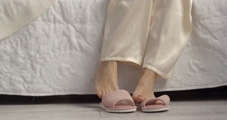 szandál : Close up of a womans pink slippers standing next to white bed. Morning concept. Stock mozgókép