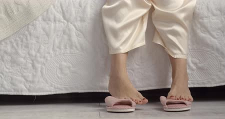 szandál : Pink fashion slippers standing next to bed in cozy bedroom.