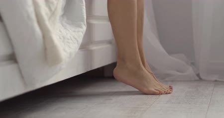 szandál : Beautiful female legs lightly touching the floor. Morning concept. Stock mozgókép