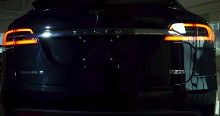 tesla motors : Back view image of Tesla car Model X with switched on headlight. Stock Footage
