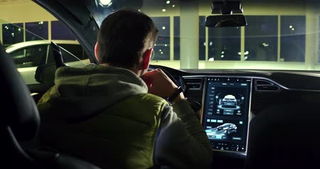 tesla car : Man observing interior od tesla car model X.
