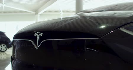 světlomety : Close up of hood, logo, headlamps of Tesla car Model X.. Electric cars show room E-Drive. Kiev, Ukraine 13 february 2018. Dostupné videozáznamy