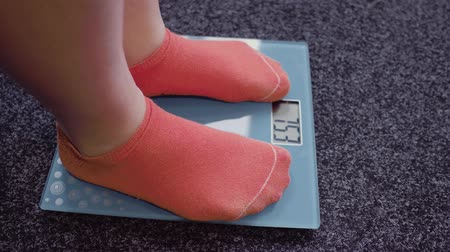 spadek : Woman feet standing on electronic scales. Weight checking concept. Wideo