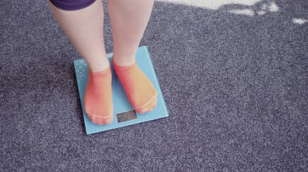 spadek : Young girl is going to check weight with the help of electronic scales. Weight loosing concept.