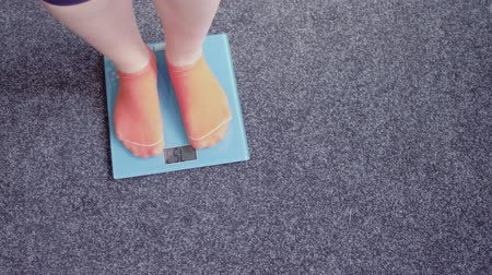 gevşek : Feet of woman in pink socks checking weight on electronic scales. Loosing weight concept. Stok Video