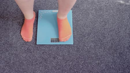 pounds : Close up of girl feet in rosy socks standing on electronic scales. Weight loosing concept.