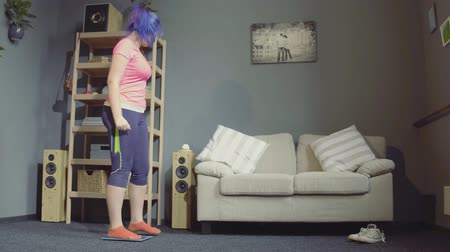 libras : Side view image of color haired girl checking her weight in cozy room. Loose weight concept.