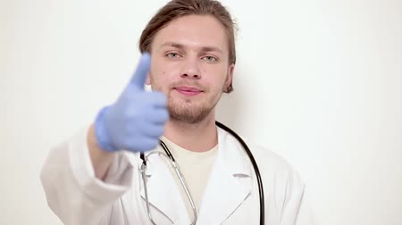 доктор : Handsome vet in medical unform posing on camera. Showing thumb. Veterinary concept.