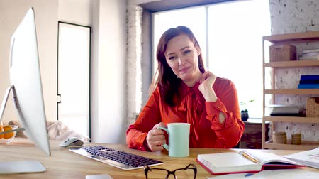 chatter : Attractive businesswoman chatting and drinking coffee. Flirty female office worker dressed in ginger coloured blouse talking and having her coffee while sitting at table. Stock Footage