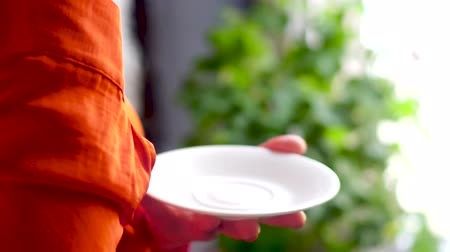 kahve molası : Female hands holding little cup and plate. Close up video of woman wearing ginger shirt holding white porcelain tea cup above white porcelain plate.