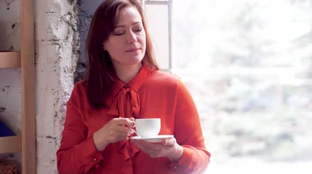 blúz : Businesswoman relaxing standing next to window with coffee. Beautiful woman wearing orange blouse drinking coffee from little porcelain cup and holding plate underneath. Window in background.